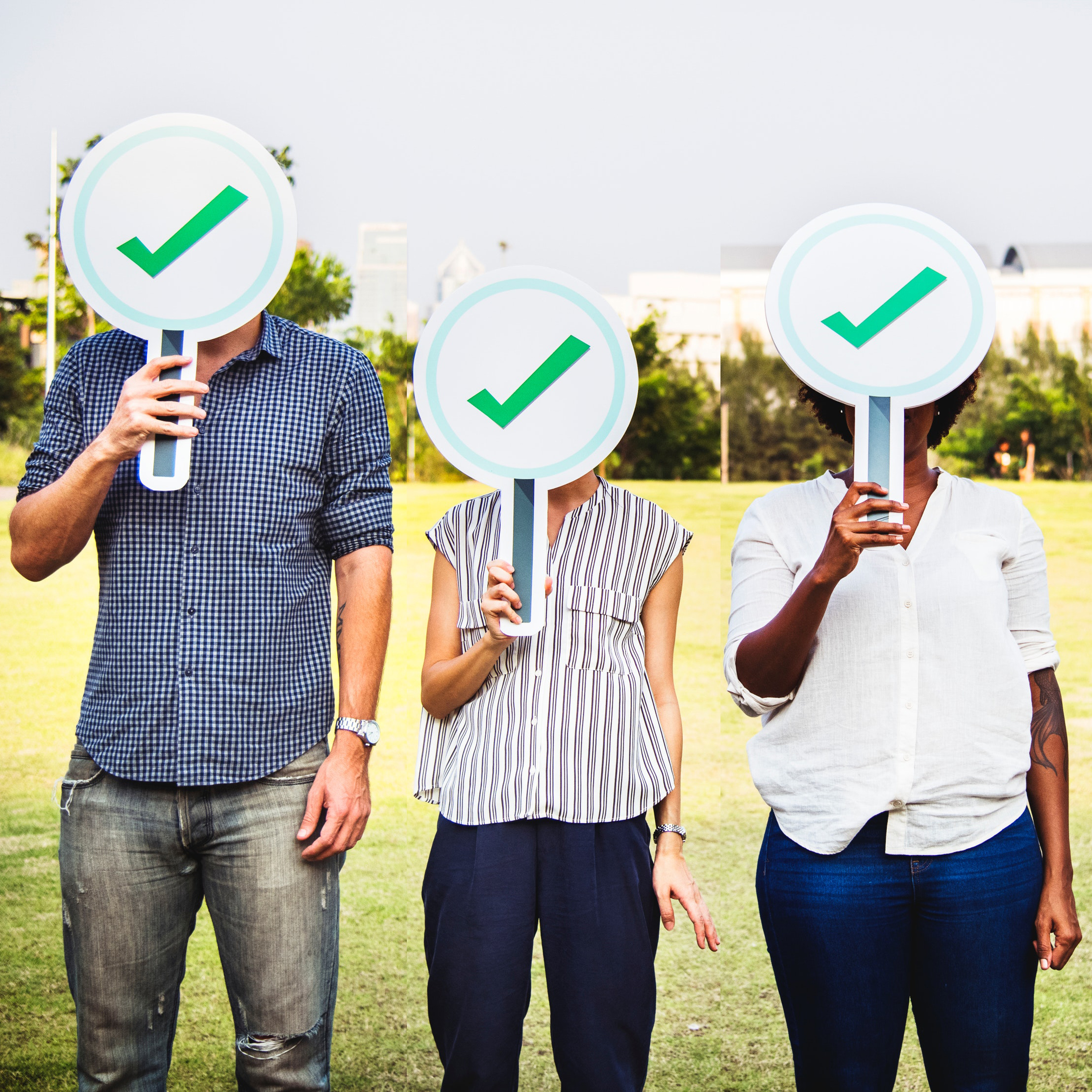 """diverse group holding signs with green checkmark"""